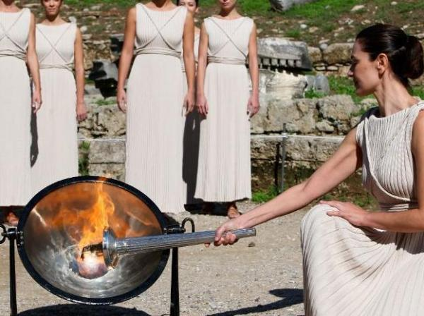 'High Priestess'/actress Maria Nafpliotou lighting the Olympic Torch from the sun's rays in a parabolic mirror